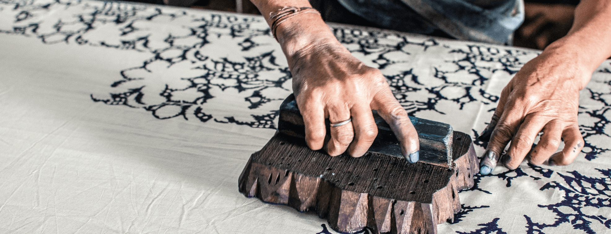 A person creating a floral print on a fabric using block printing method